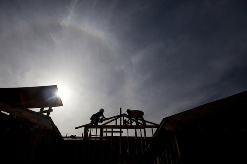 Workers construct a home in Rancho Santa Fe in San Diego County. The 30-year mortgage rate averaged 4.52% as the year began and was 4.39% last week.