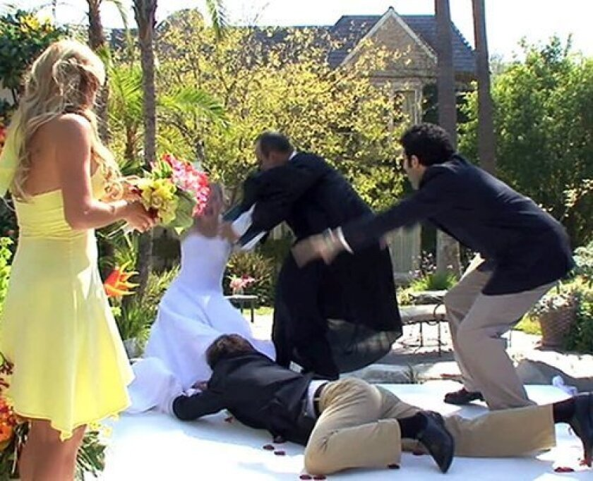 "A shot of the YouTube video ""My Clumsy Best Man Ruins Our Wedding,"" which shows a bride being knocked into a pool while performing her wedding vows. Many viewers thought the video was of a real wedding, but it was revealed later to be the trailer for the film ""Chloe and Keith's Wedding."""