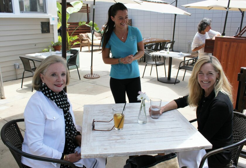 Piazza 1909 lunch guests Anne Gilchrist (left) and Laura McDonald chat with waitress and bartender Patricia Casero.