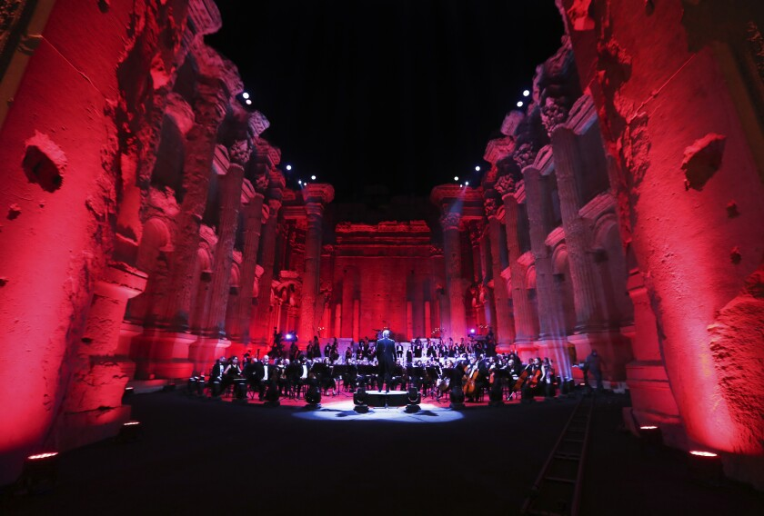 """Musicians from the Lebanese Philharmonic Orchestra perform during a concert in the ancient northeastern city of Baalbek, Lebanon, Sunday, July 5, 2020. Dubbed """"an act of cultural resilience,"""" the concert aims to send a message of unity and hope to the world amid the coronavirus pandemic and an unprecedented economic and financial crisis in Lebanon. For the first time since the Baalbek International Festival was launched in 1956, this year's concert is being held without an audience, in line with strict COVID-19 guidelines. Instead, it is being broadcast live on local and regional TV stations and live-streamed on social media platform. (AP Photo/Bilal Hussein)"""