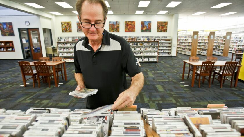 Vista resident Dan Webster searches for music CDs during his visit to the Vista Library on Thursday.