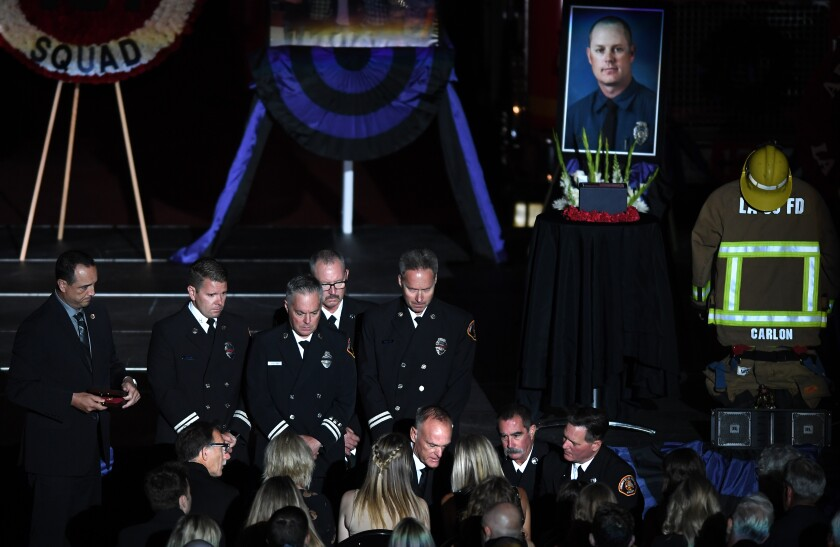 A photo of Tory Carlon is seen behind firefighters at a memorial