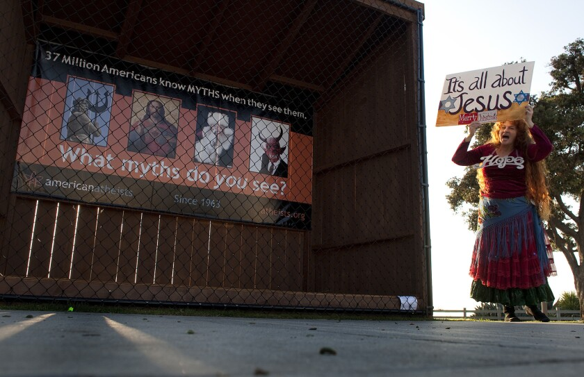 A Christian woman protests in front of an atheist group's display where Nativity scenes use to be at Pacific Palisades Park along Ocean Avenue in Santa Monica in 2011.