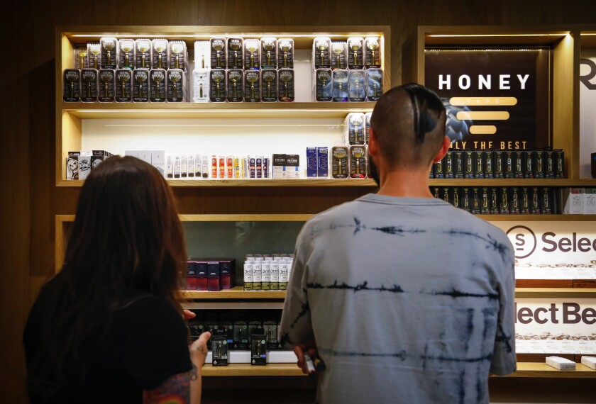 Tina Glen (left) and Nick Isordia look at the vaping products at March and Ash, a cannabis dispensary in Mission Valley.