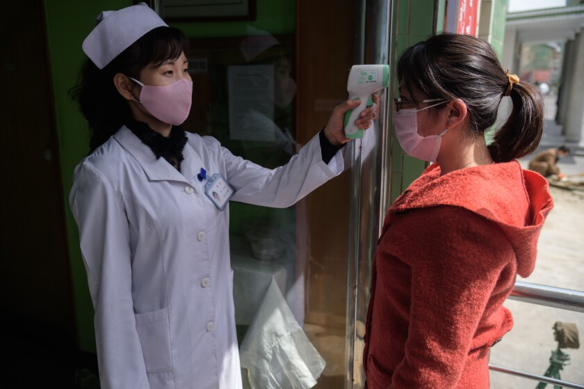 A health worker takes a woman's temperature at an entrance of the Pyongchon District People's Hospital in Pyongyang.