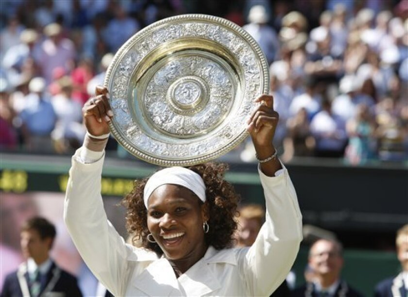 Serena Williams holds the championship trophy, after defeating her sister Venus to win the women's singles final on the Centre Court at Wimbledon, Saturday, July 4, 2009. (AP Photo/Kirsty Wigglesworth)