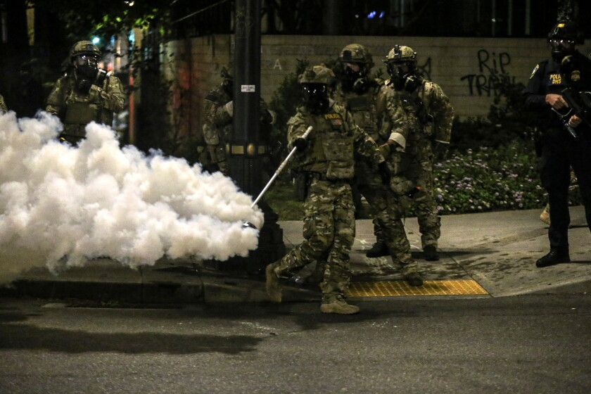 Militarized federal agents deployed by President Trump to Portland, Ore., fire tear gas against protesters Friday.