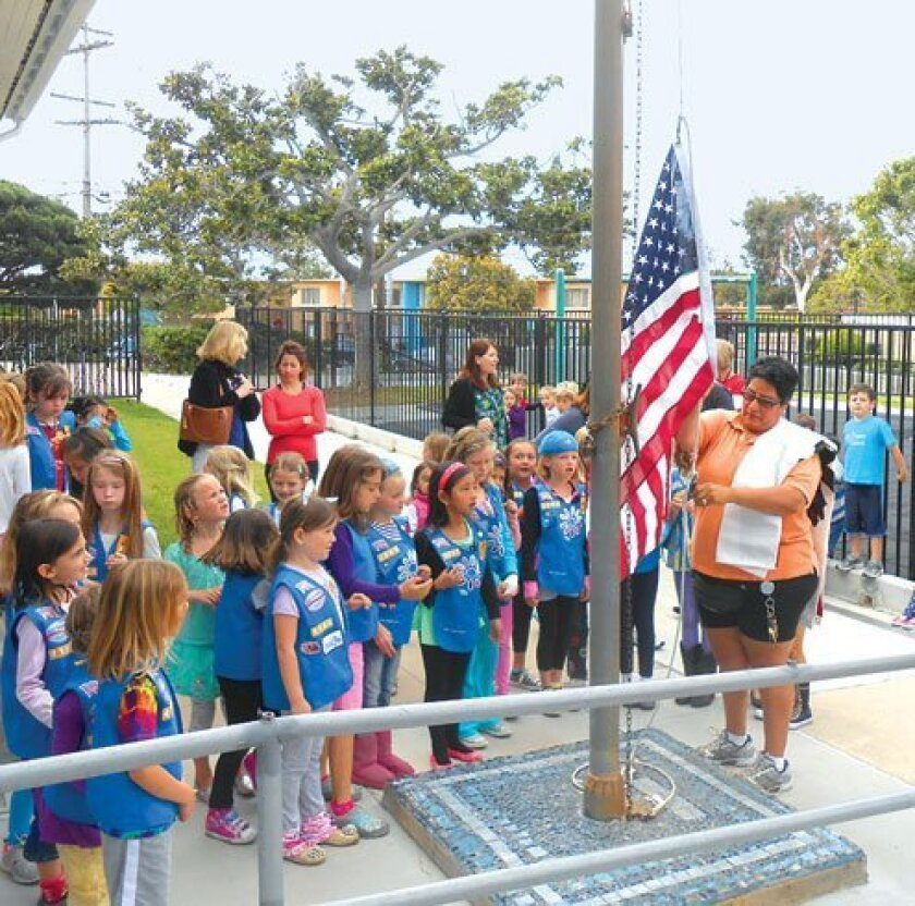La Jolla Girl Scout Daisy Troops 3869 and 4186 watch the raising of the flags they purchased for Bird Rock Elementary School.