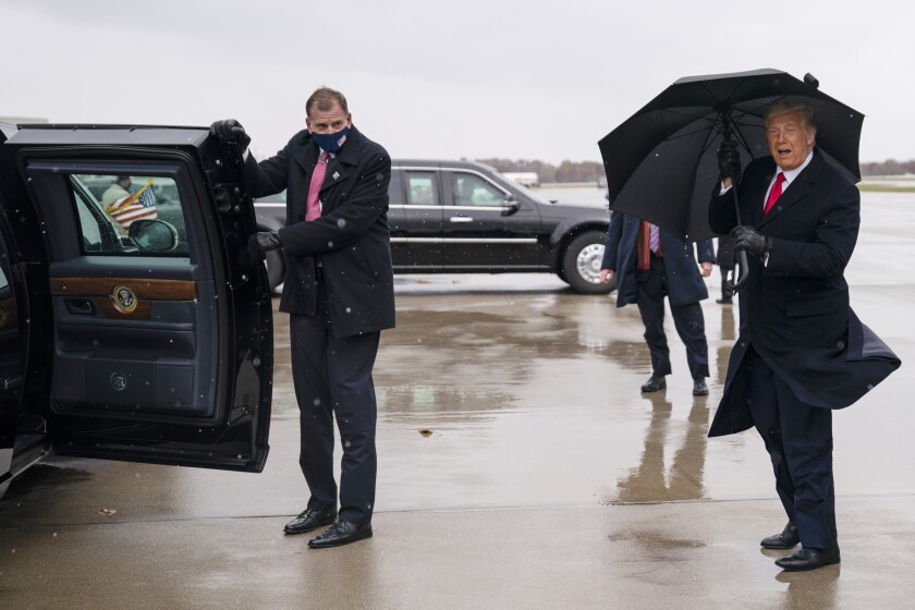 A man in a mask holds open the door of Trump's limo as the president holds an umbrella against the wind and rain.