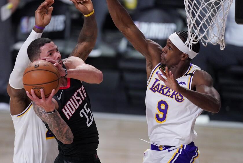 Houston's Austin Rivers grabs a rebound in front of the Lakers' Rajon Rondo.