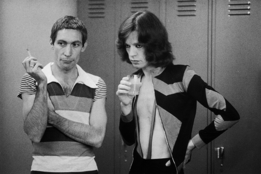 Charlie Watts, holding a cigarette, and Mick Jagger, with a drink, during the Rolling Stones' tour of the Americas in 1975.