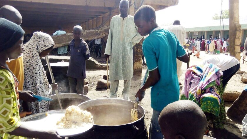 A man serves lunch from an open-air kitchen for people displaced by Boko Haram violence on May 19, 2016, in the Dalori Internally Displaced People's Camp near Maiduguri, northeast Nigeria.