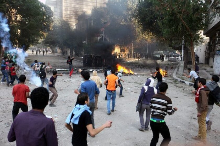 Egyptian opponents of President Mohamed Morsi throw stones at antiriot security forces Wednesday during clashes in Tahrir Square in Cairo.