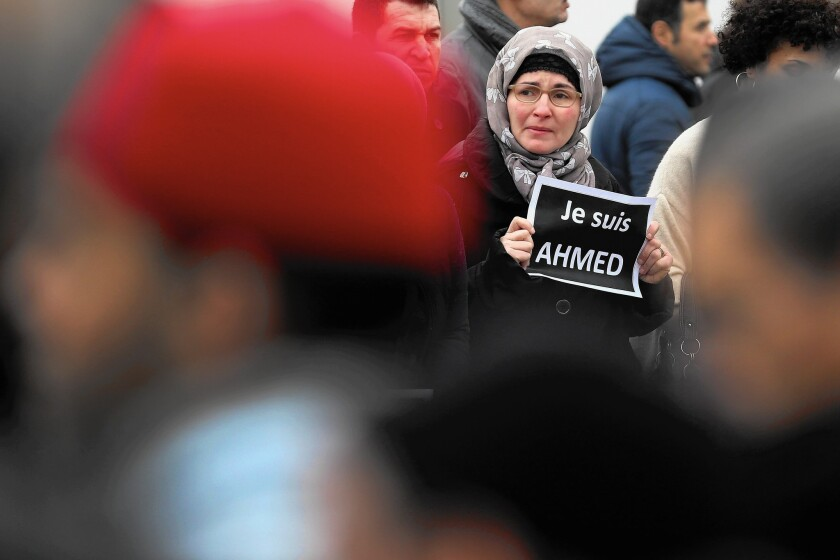 "A mourner holds an ""I am Ahmed"" sign during the funeral of police Officer Ahmed Merabet at a mosque in Bobigny, France. Merabet was killed by terrorists during the attack on Charlie Hebdo magazine."