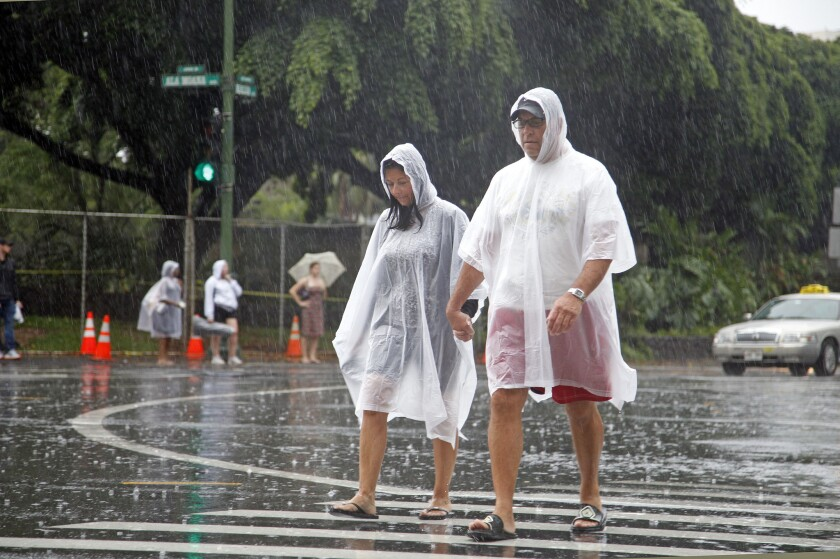 Tourists cope with wet weather in Waikiki in Honolulu Sunday.