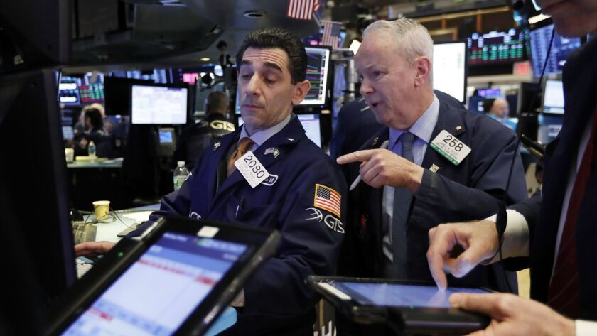 Specialist Peter Mazza, left, and trader James Riley work on the floor of the New York Stock Exchange on Tuesday.