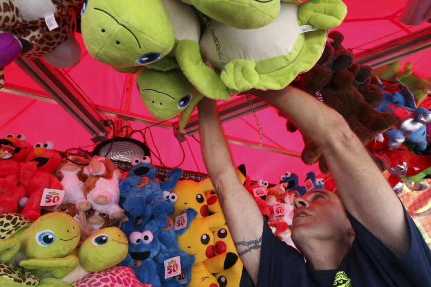 Michael Gilliam puts up stuffed animal prizes at the Balloon Pop carnival game at the San Diego County Fair on Thursday at the Del Mar Fairgrounds. The fair opens Friday, May 31.