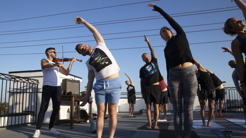 Yoga instructor Jake Ferree and violinist Volkan Can Canbolat team up for Vinyasa & Violin on the roof of Palihouse in West Hollywood.