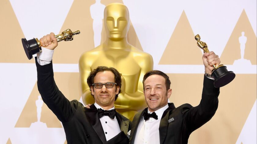 "Producer Dan Cogan, left, and director Bryan Fogel, winners of the documentary feature award for ""Icarus,"" pose in the press room at the 90th Academy Awards."