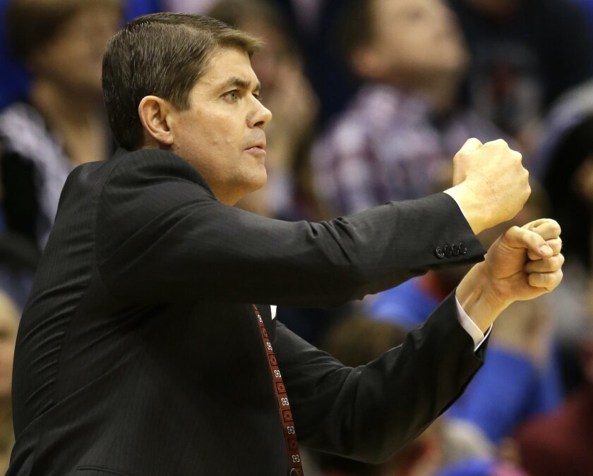 FILE - In this Jan. 4, 2015, file photo, UNLV head coach Dave Rice directs his team during the first half of an NCAA college basketball game against Kansas in Lawrence, Kan. After missing the NCAA Tournament the past two seasons, the expectations in Sin City are that the Runnin' Rebels should be ba