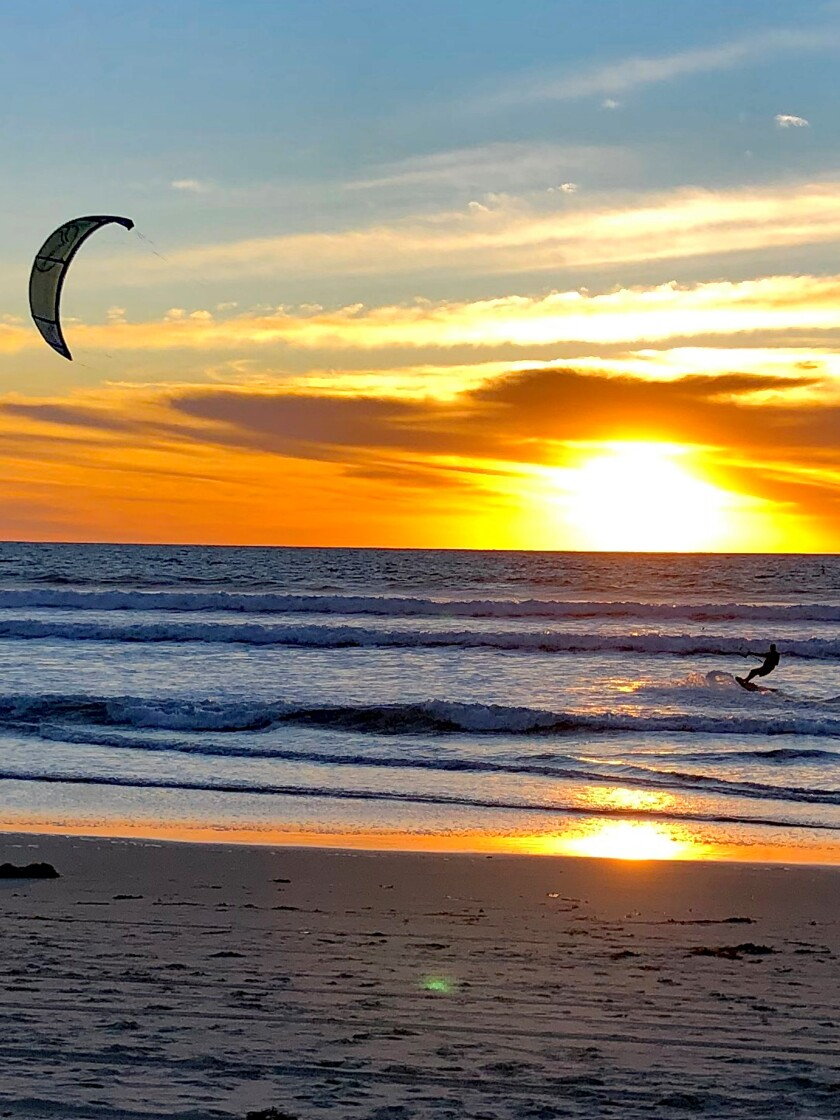 Jeff Raney enjoys kitesurfing at sundown in the waters off Pacific Beach.