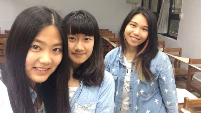 Wang Hao, left, a university undergraduate from northeastern China, poses with a fellow mainland Chinese student, center, and a local classmate at Ming Chuan University in Taipei, Taiwan.