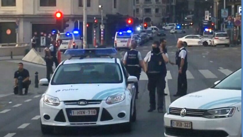 In this image taken from video, police cars block a road near the train station in central Brussels,