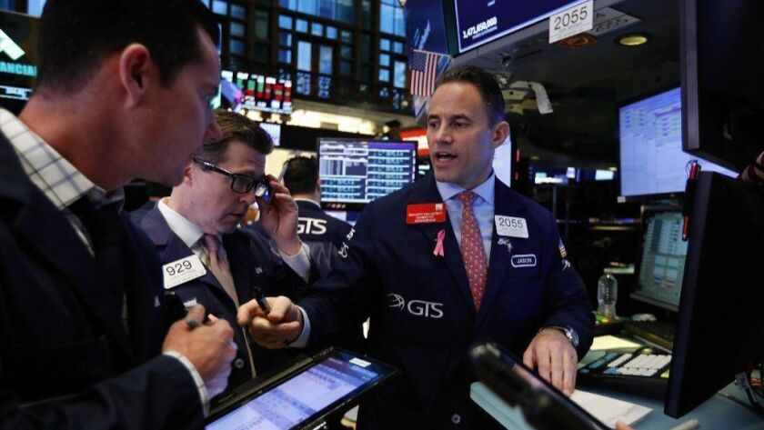 Specialist Jason Hardzewicz, right, works on the floor of the New York Stock Exchange on, Oct. 24, 2018, a day of steep market declines. Futures for the Dow Jones Industrial Average and the Standard & Poor's 500 were higher on Oct. 25, suggesting a likely revival of buying.