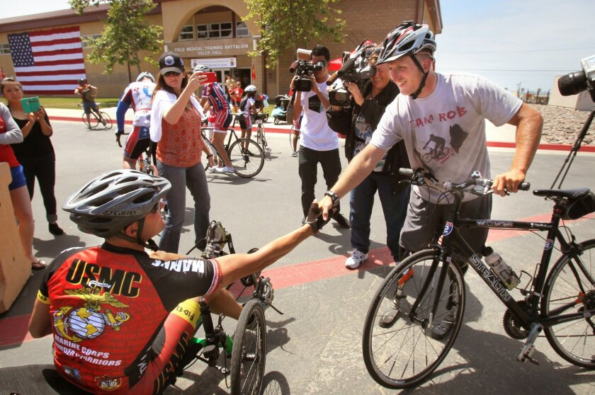 Rob Jones, at right, shakes hands with Gunnery Sgt. Matthew Hammond who was also injured in Afghanistan. Hammond and others rode with him through the base.