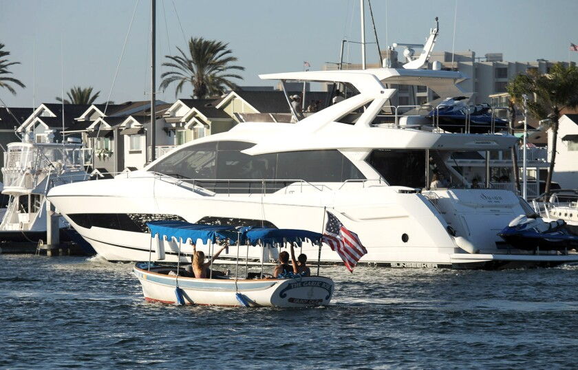 Small boats and yachts sail together in the 2021 War Heroes on Water Boat Parade.