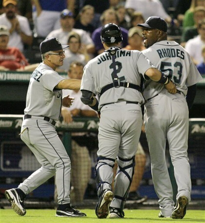 Seattle Mariners, from right to left, relief pitcher Arthur Rhodes yells at home plate umpire Paul Nauert (not shown) while being joined by catcher Kenji Johjima and first base coach Eddie Rodriguez after Rhodes was ejected in the eighth inning of a baseball game against the Texas Rangers, Wednesday, July 30, 2008, in Arlington, Texas. Texas won 4-3. (AP Photo/Matt Slocum)
