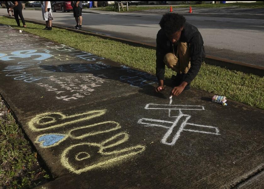 Lenar Nesmith, of Pompano Beach, Fla., a fan of rap singer XXXTentacion, writes a message on the sid