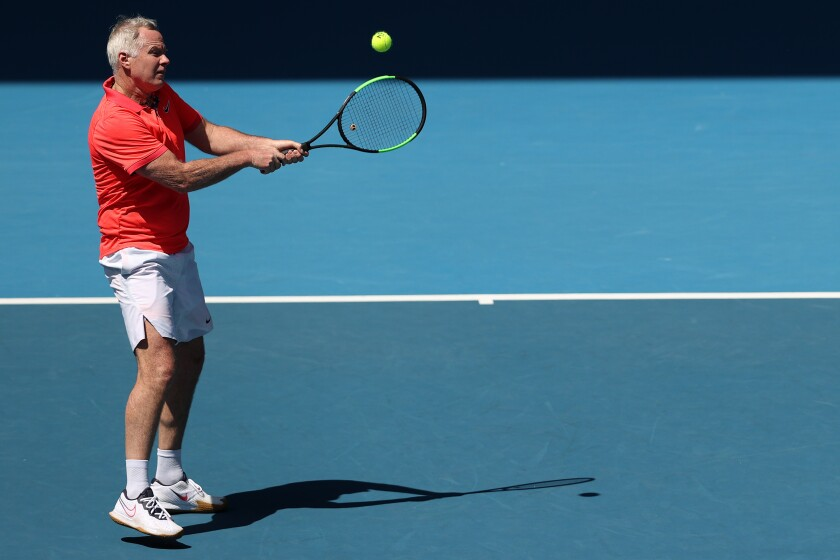 Patrick McEnroe plays a backhand during a men's legends doubles match with brother John McEnroe at the Australian Open in January.