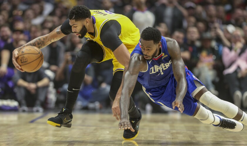 Lakers forward Anthony Davis (3) tries to control ball as he's defended by Clippers forward JaMychal Green (4) during the first half Oct. 22.