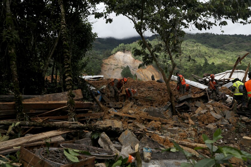 Rescue teams search for survivors after a rain-fueled landslide in the village of Queja, Guatemala, on Saturday.