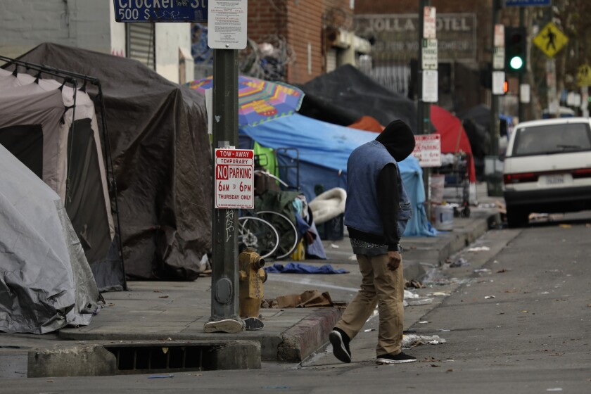 A man walks down 6th Street, weaving his way around tents, in Los Angeles.