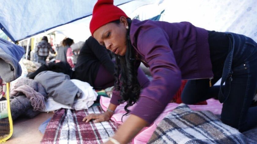 A group of transgender women traveling with the caravan of Central Americans take shelter underneath a tarp while the light showers pass by. Shannel Smith 28, from Honduras cleans her sleeping area.