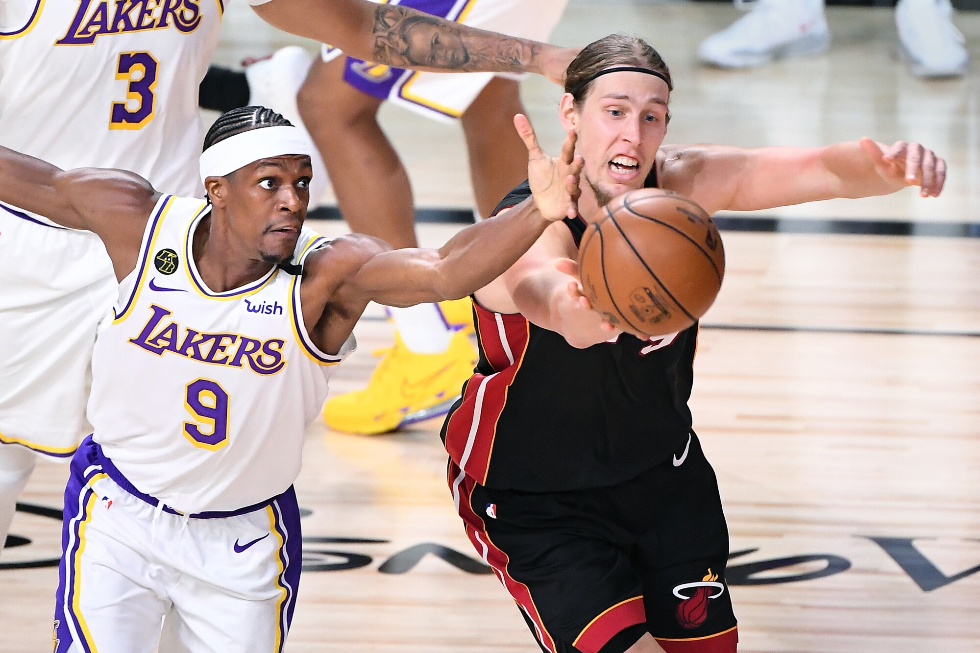 Lakers guard Rajon Rondo and Heat center Kelly Olynyk chase after a loose ball during Game 3 on Sunday night.