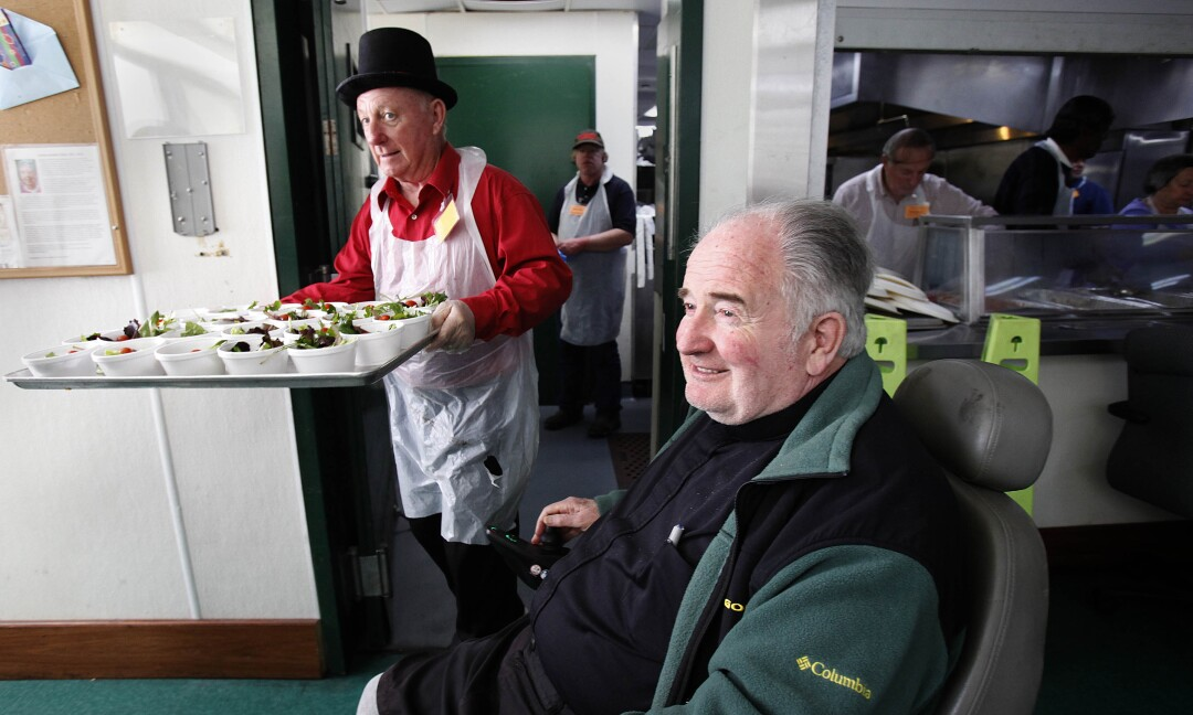 Steve Conner, left, brings out a tray of individual salads near Father Joe Carroll