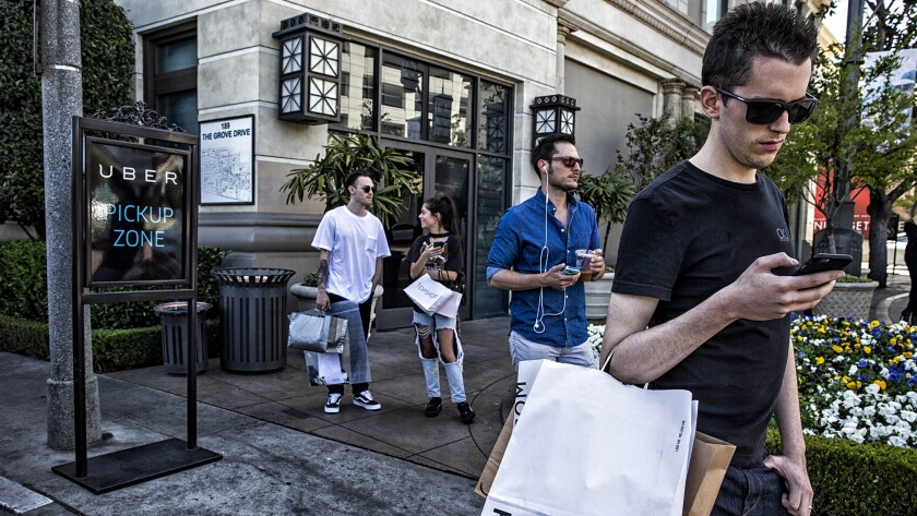 Shoppers at the Grove wait for Uber and Lyft rides in a designated zone on the east side of the prop