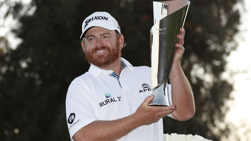 J.B. Holmes holds up the winner's trophy on the 18th green at the conclusion of the Genesis Open on Sunday at Riviera Country Club.