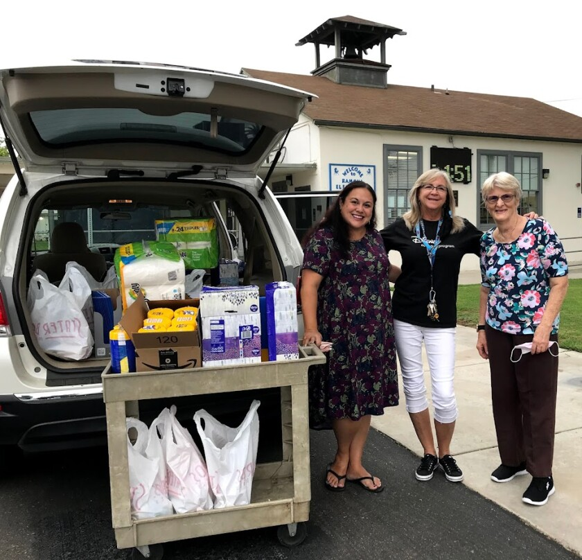 Mary Halliday, left, and Tiffany Lynch, right, present Ramona Elementary Principal Pixie Sulsar with school supplies.