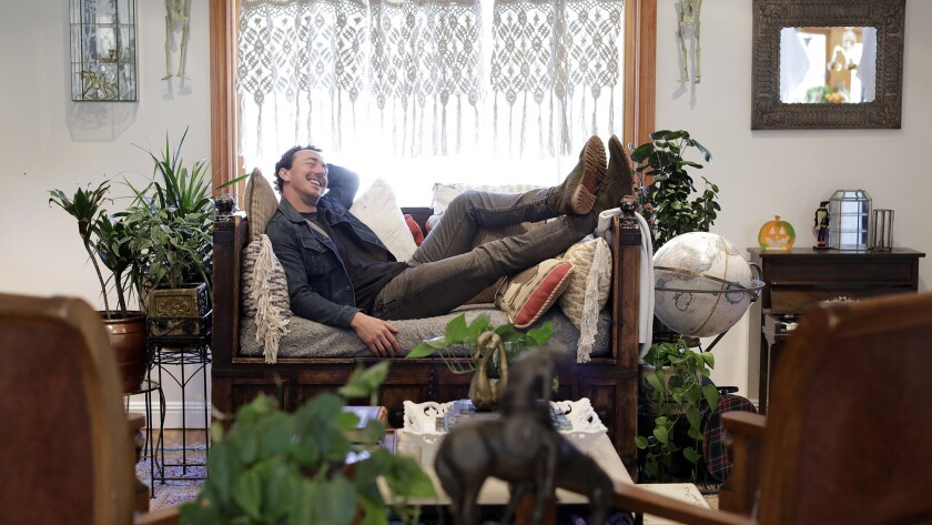 "Actor Chris Coy's favorite room is his living room and adjacent kids' room. He enjoys lounging in his opium chair reading scripts. The space is decorated in ""Alice's style"" named for his wife. Wood and leather provide a warm, rustic feel."