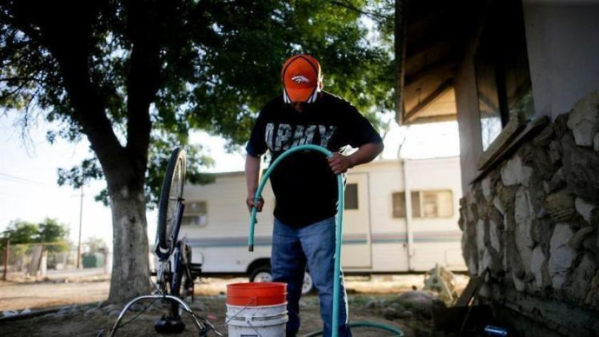 A man gets water from a hose in Tulare County, home to several communities with unsafe water supplies.