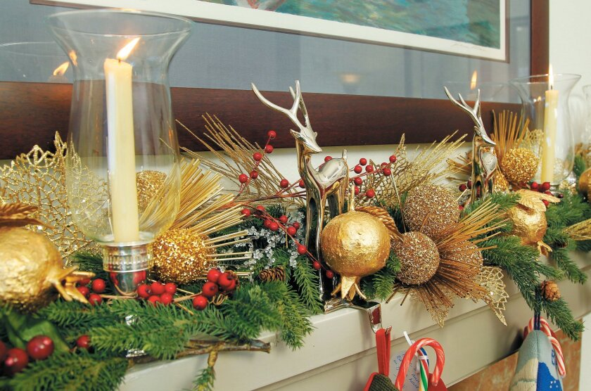 Red berries add a pop of color, complementing the metallic decorations on the fireplace mantel.