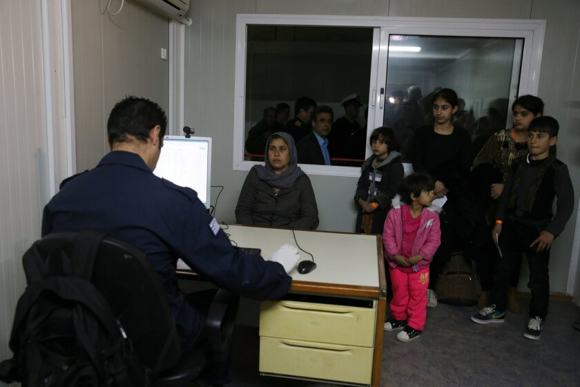 A policeman prepares to take a photograph of a woman as children wait for their turn at a registration and hospitality center for refugees and migrants, known as a hotspot, on the eastern Greek island of Chios, Tuesday, Feb. 16, 2016. Greek Defense Minister Panos Kammenos said that military teams h