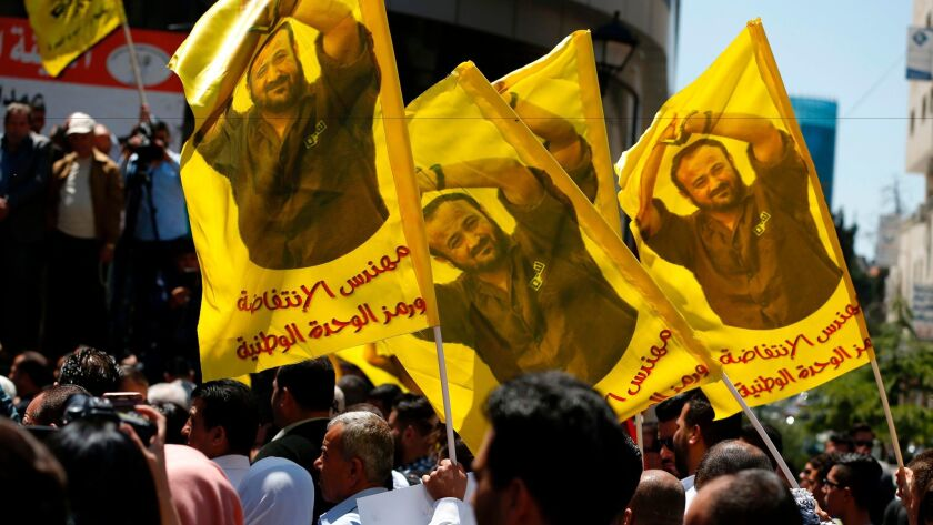Protesters wave flags bearing a portrait of prominent jailed Palestinian Marwan Barghouti during a r