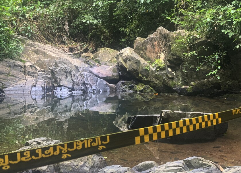 FILE - In this Aug. 6, 2021, file photo, police tape cordons off the area where a woman was found dead a day earlier at a secluded spot on the southern island of Phuket, Thailand. A suspect in the death of a 57-year-old Swiss woman on Thailand's tourist island of Phuket was charged with murder and robbery, police said Sunday. (AP Photo, File)