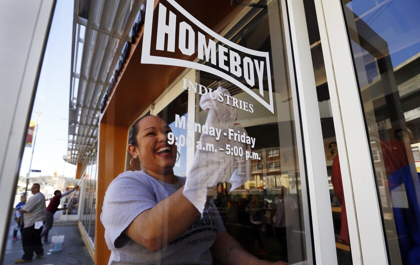 Ilenee Velasco cleans the front door of the headquarters of Homeboy Industries in March. Nonprofits that hire and train disadvantaged and out-of-work clients, such as Homeboy, won't have to pay them Los Angeles' new minimum wage for the first year and a half of their employment.