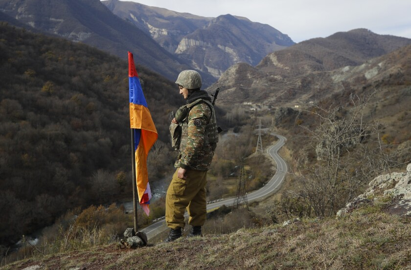 FILE - In this Wednesday, Nov. 25, 2020 file photo, An ethnic Armenian soldier stands guard next to Nagorno-Karabakh's flag atop of the hill near Charektar in the separatist region of Nagorno-Karabakh at a new border with Kalbajar district turned over to Azerbaijan. Armenia's Defense Ministry is reporting that three of its troops were killed and two more were wounded in clashes with Azerbaijani forces on the border between the two ex-Soviet nations. The two countries have been locked in a decades-long tug-of-war over the Nagorno-Karabakh region, and they accused each other of starting the clashes on Wednesday, July 28, 2021. (AP Photo/Sergei Grits, File)
